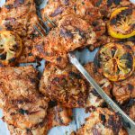grilled Aleppo pepper chicken on a platter with grilled lemons