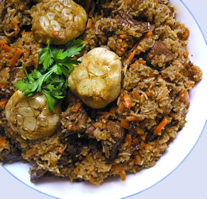 Plov: Lamb and rice and whole roasted bulbs of garlic in a bowl, garnished with parsley.