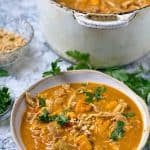 a bowl and part of a pot, both filled with peanut chicken stew with sweet potatoes and sprinkled with chopped cilantro