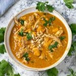 a white bowl filled with peanut chicken stew with sweet potatoes, garnished with chopped cilantro