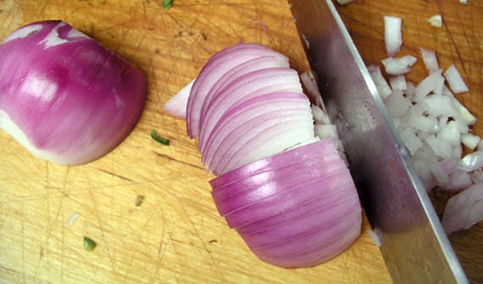 close up of a red onion being sliced into perfect dice