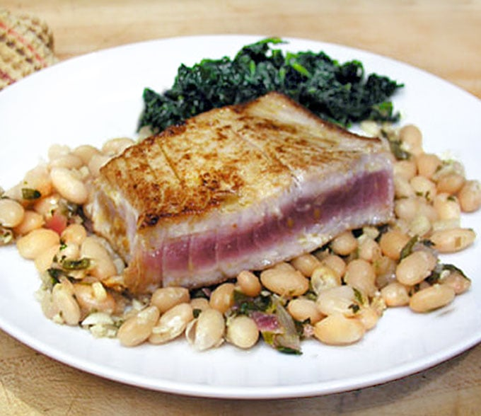 rare seared tuna stead on top of a plate of white beans