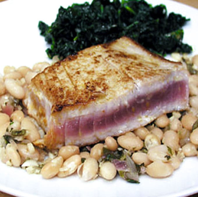 close up of a rare tuna steak, seared and on top of Peruvian white beans