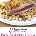 a piece of seared rare tuna steak atop a plate of white beans, with wilted kale