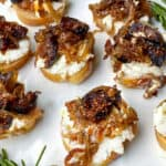 7 crostini topped with creamy goat cheese, caramelized onions and figs, sprigs of rosemary around the plate