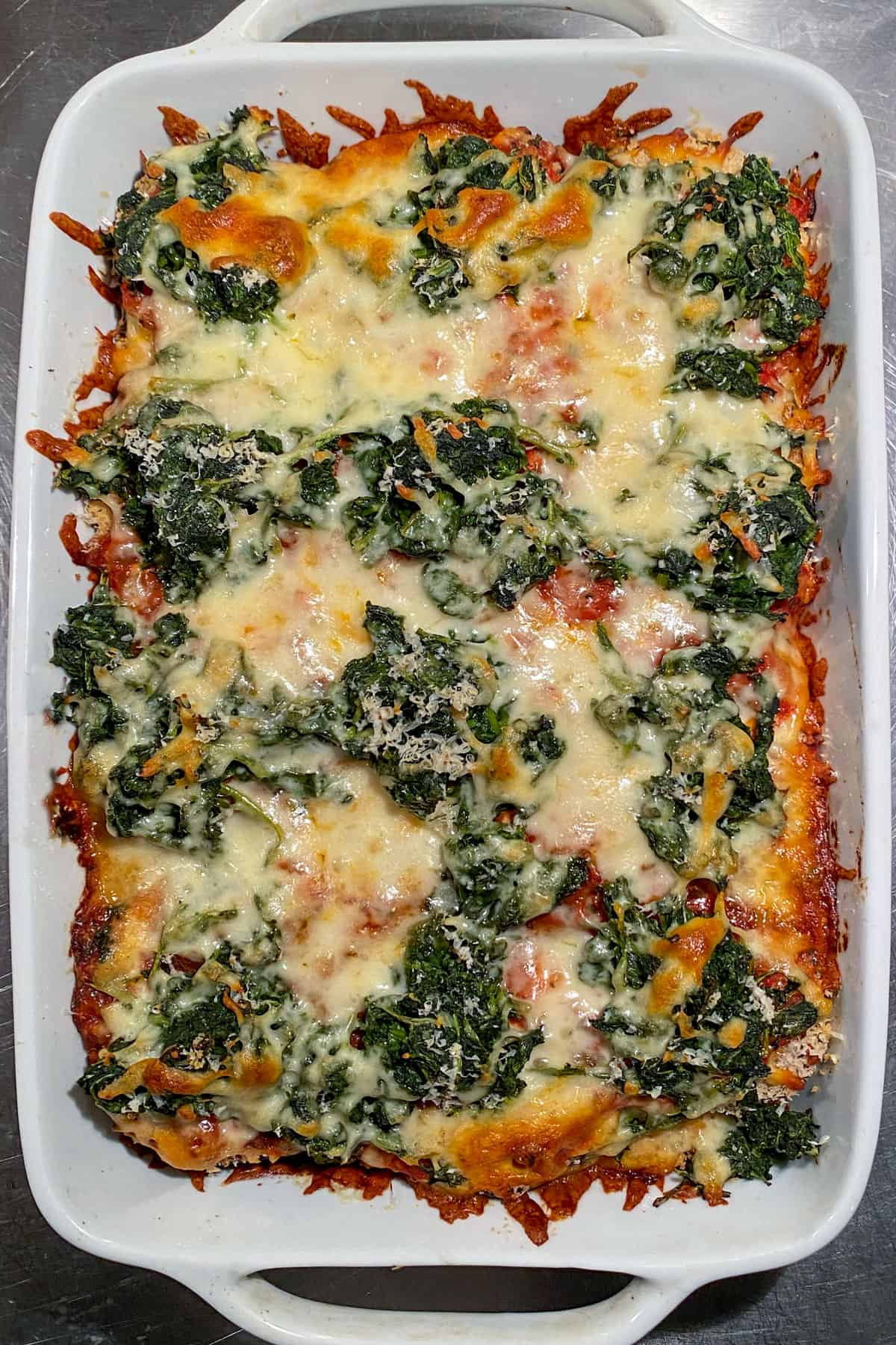 baked eggplant parmesan topped with spinach and cheese, in a white rectangular casserole dish, seen from above