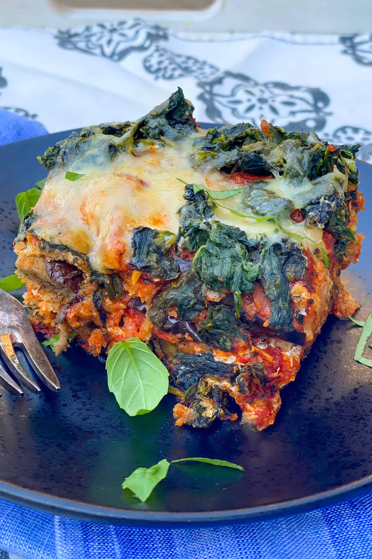 slice of eggplant parmesan topped with spinach and cheese, on a black plate, with a few pieces of slivered basil on top