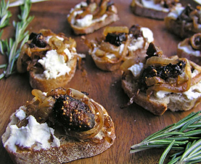 5 pieces of Goat Cheese Caramelized Onion and Fig Bruschetta on a wooden serving plate with rosemary sprigs