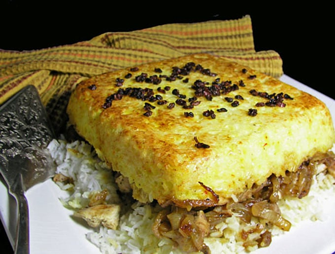 Persian Layered Chicken and Rice with Yogurt is a wonderful dish with layers of tender chicken, caramelized onions and saffron rice cooked in a casserole. The casserole is flipped over so the bottom layer, with its beautiful golden crust, becomes the top. It's served with garlicky yogurt sauce on the side.