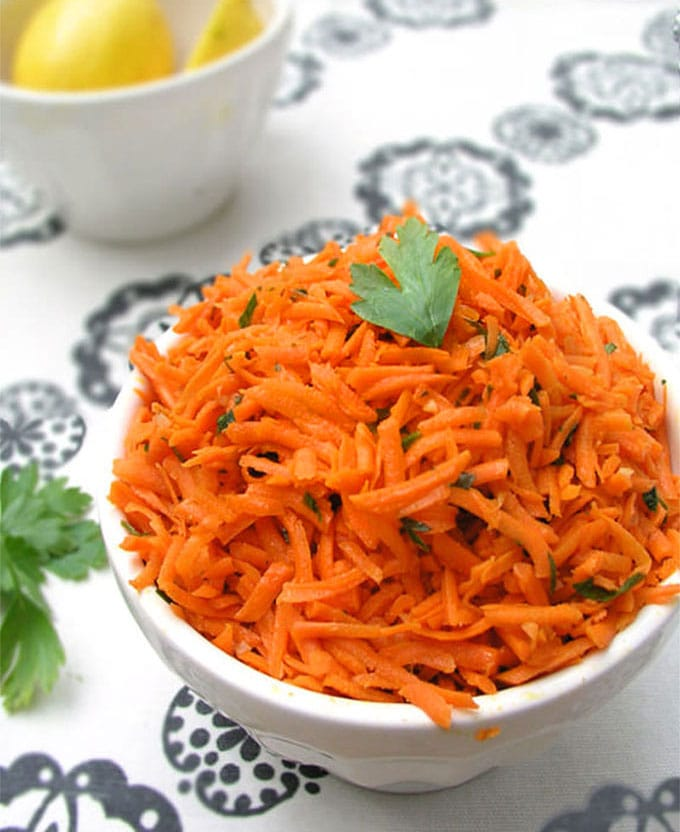 a bowl over filled with shredded Moroccan raw carrot salad and a sprig of parsley on top