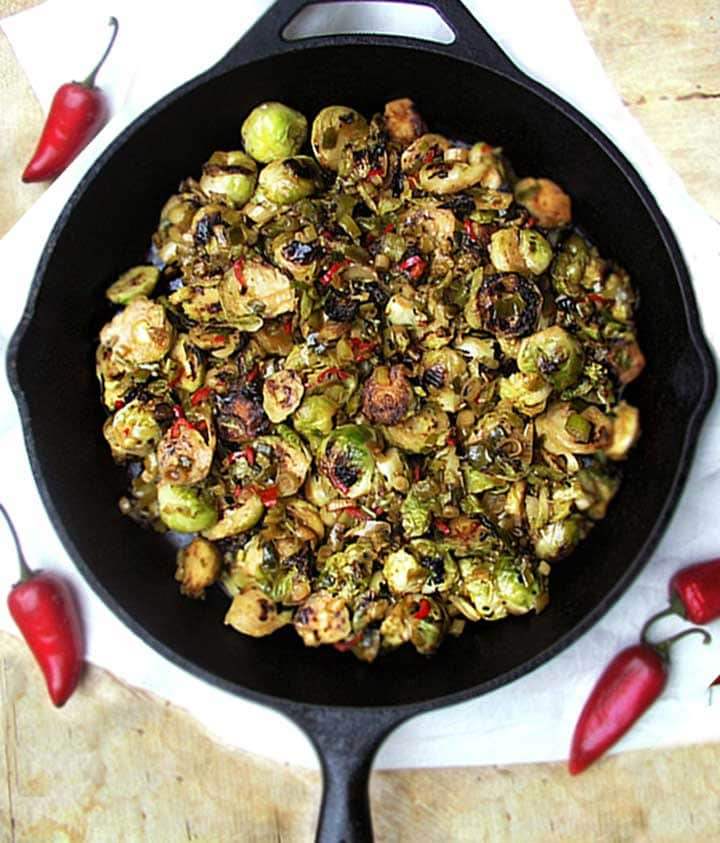 cast iron skillet with sliced, browned brussels sprouts with maple chili sauce.