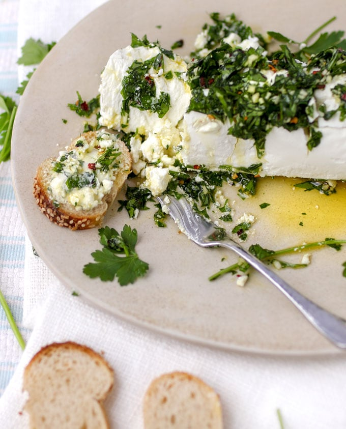a lot of goat cheese on a plate topped with chopped parsley and olive oil and spices.