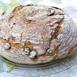 a loaf of homemade no-knead Olive bread on a cooling rack