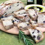No knead olive bread slice and on a round wooden platter with olive oil and balsamic in a shallow bowl for dipping