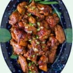 dark blue oval platter with glazed lime apricot baked chicken wings, sprinkled with scallions