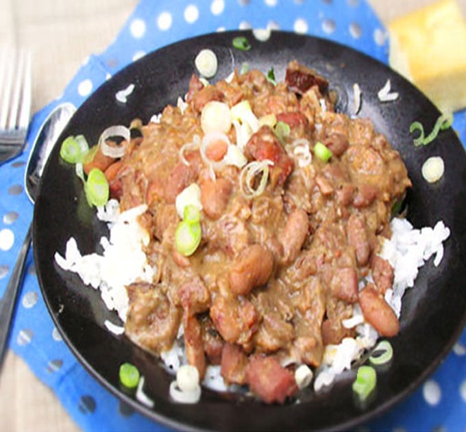 Red Beans and Rice in a black bowl with chopped scallions on top.