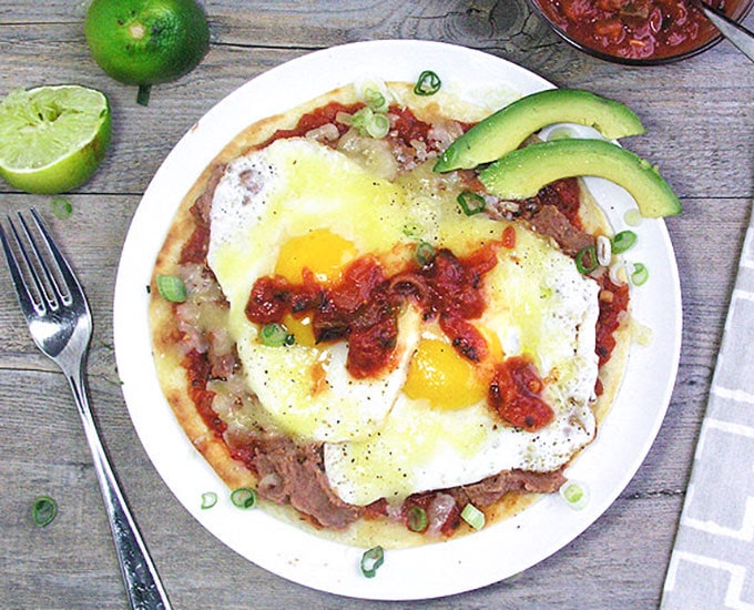 Huevos Rancheros is a hearty dish of eggs, beans, cheese and salsa layered on top of a corn or flour tortilla. It's a great breakfast but also a fantastic dish for lunch or family dinner. This recipe shows you how to make quick and easy huevos rancheros for a crowd l www.panningtheglobe.com