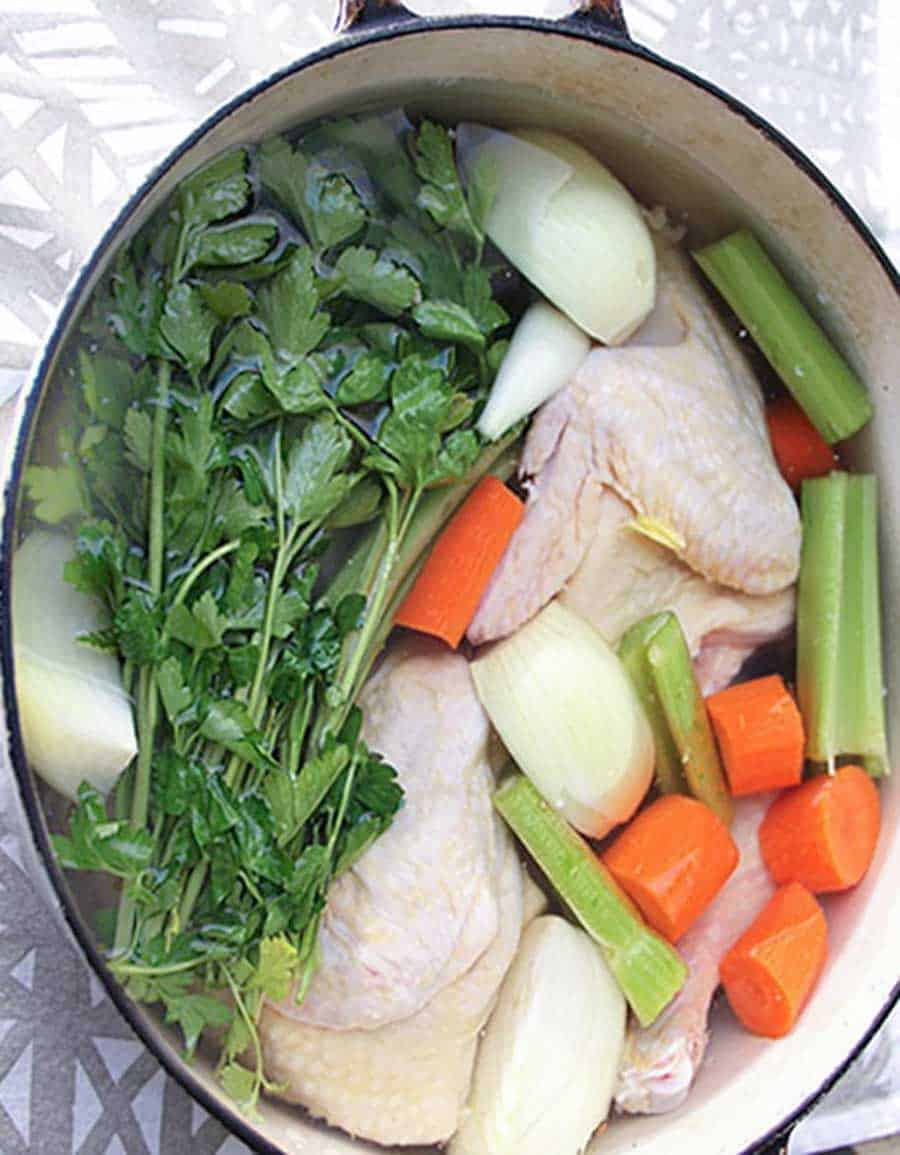white oval Dutch oven filled with ingredients to make chicken soup from scratch: raw chicken, onions, carrots, celery and parsley