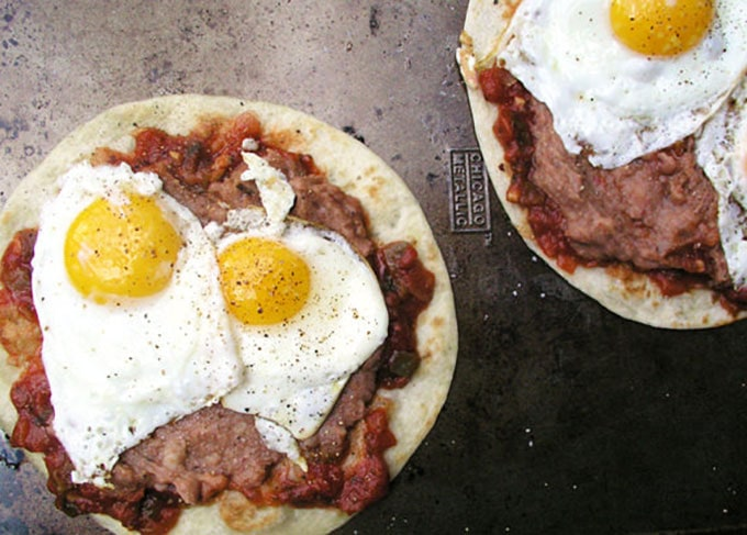 salsa, fried eggs and refried beans on two flour tortillas: how to make huevos rancheros.