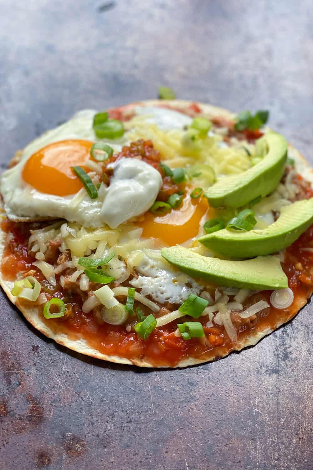 huevos rancheros: a flour tortilla on a sheet pan topped with salsa, refried beans, two sunny side up eggs, grated cheese, sliced avocados and chopped scallions.