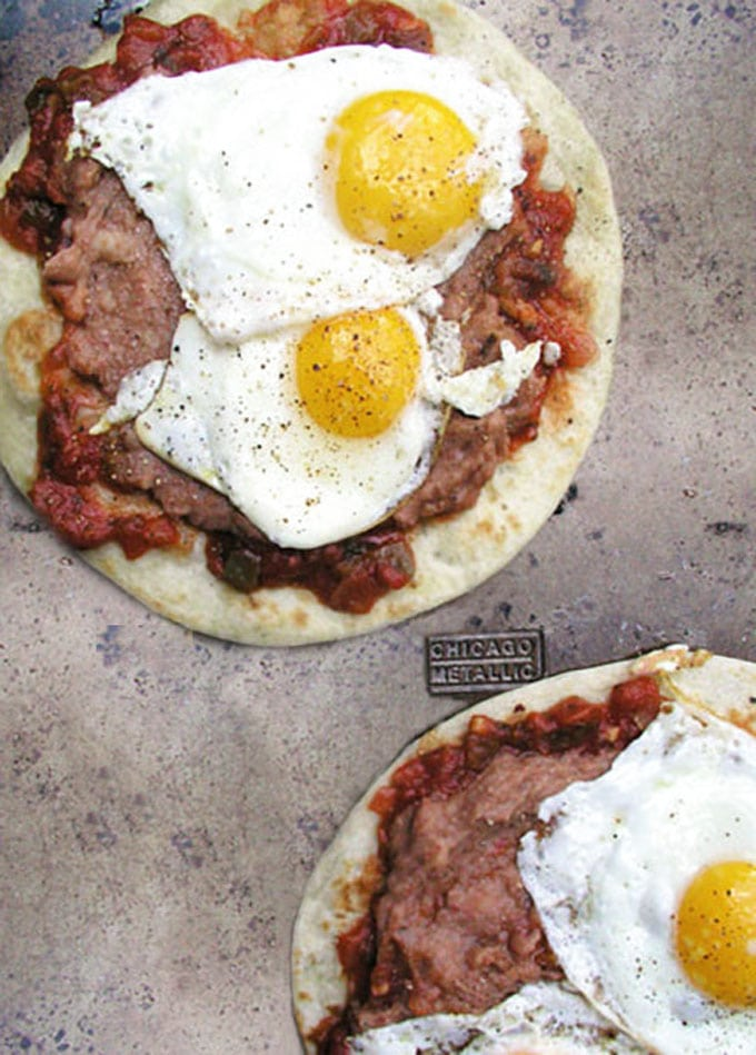 how to make huevos rancheros: tortillas topped with salsa, refried beans and fried eggs