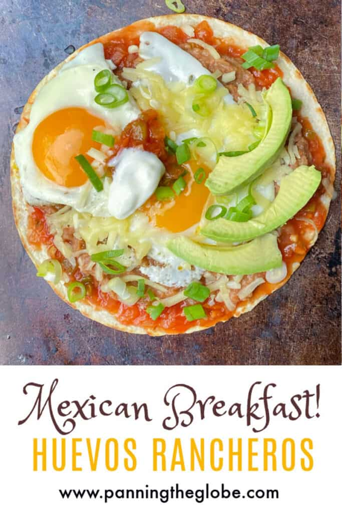 Pinterest pin with huevos rancheros on a copper colored baking sheet: a flour tortilla topped with salsa, refried beans, two fried eggs, shredded cheese and three slices of avocado
