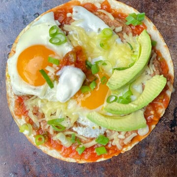 huevos rancheros on a copper colored baking sheet: a flour tortilla topped with salsa, refried beans, two fried eggs, shredded cheese and three slices of avocado