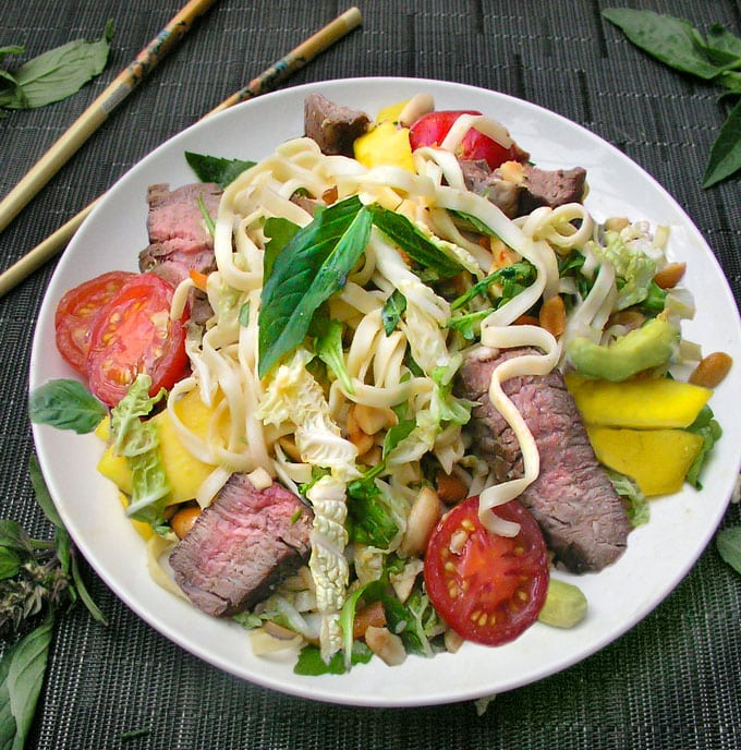 Thai Steak and Noodle Salad on a plate with mango, cabbage, basil , tomatoes and peanuts