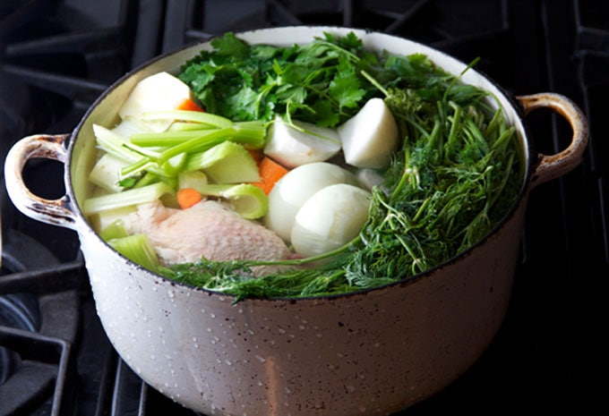 a white dutch oven filled to the brim with chicken, veggies and herbs, ready to make chicken soup