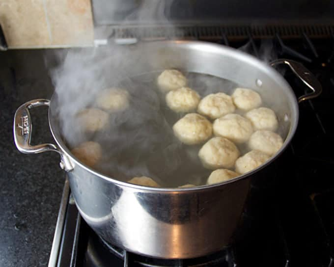 20 matzo balls simmering in a metal pot of boiling water