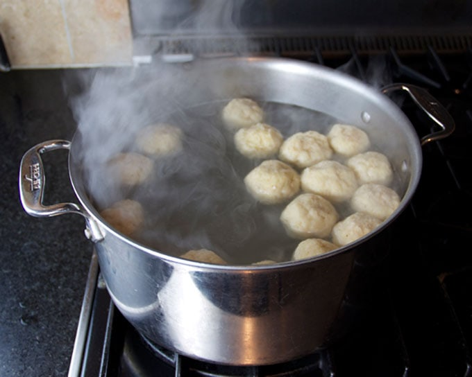 homemade matzo balls floating in a pot