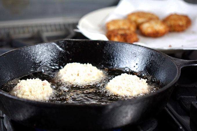 3 Royal Thai Crab Cakes sautéing in a cast iron skillet