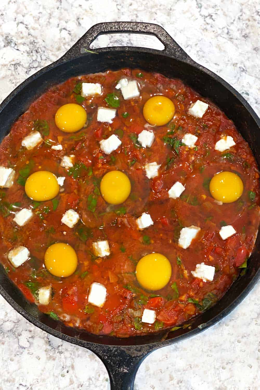 how to make shakshuka, raw eggs and feta in rich thick tomato sauce in a cast iron skillet, ready for the oven