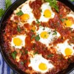 shakshuka in a cast iron skillet with parsley sprigs to garnish