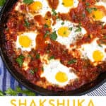 shakshuka in a cast iron skillet with 6 eggs poached in spicy tomato sauce