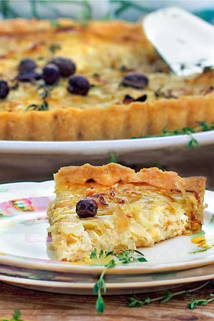 A slice of french onion tart in the foreground with the rest of the tart in the background