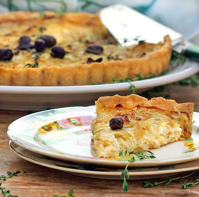 a china plate topped with a triangular slice of a French onion tart with a nicoise olive on top, the rest of the tart in the background.