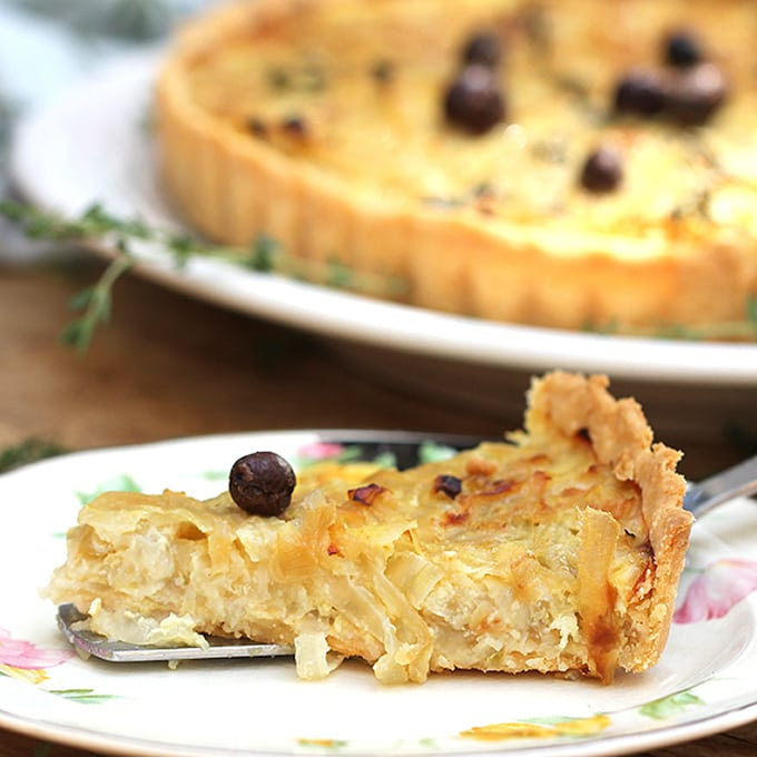close up of a slice of French onion tart topped with one nicoise olive, the rest of the tart blurred a bit in the background