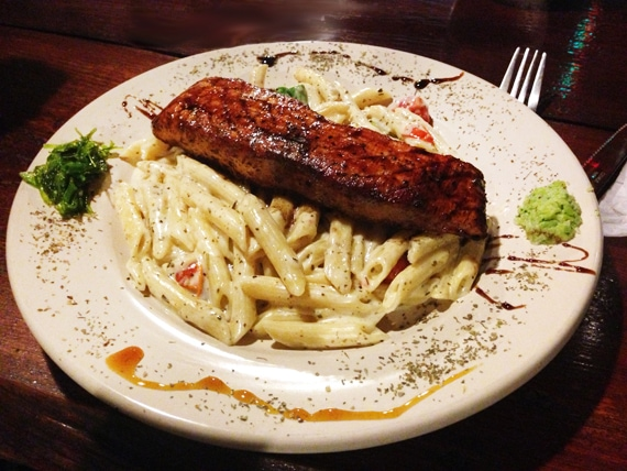 salmon on a bed of pasta alfredo