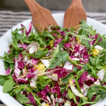 White bowl on a black and white striped dish towel, filled with tricolore salad: arugula, radicchio and endive, with wooden salad spoons in the bowl.