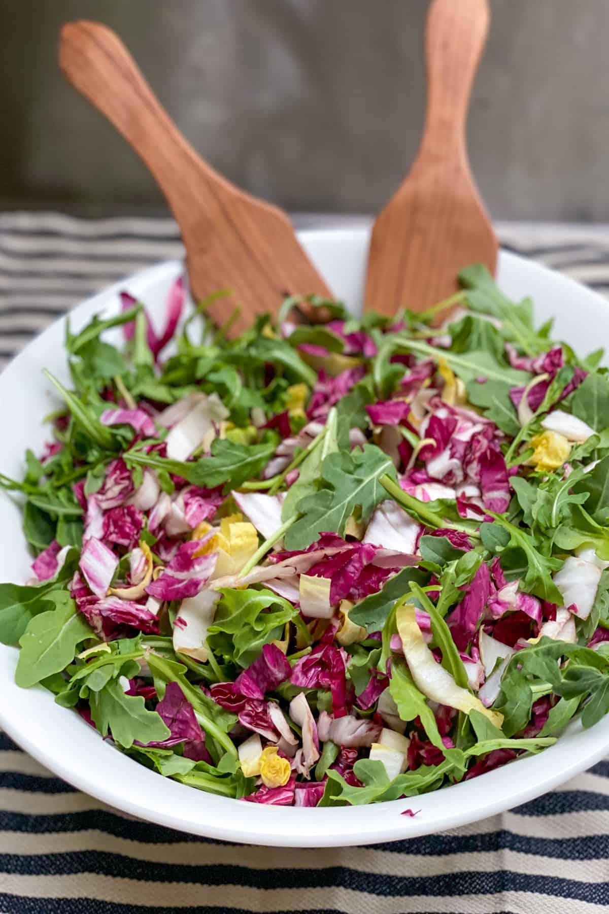 a white bowl on a black and white striped dish towel, filled with arugula, radicchio and endive, with wooden salad spoons in the bowl.