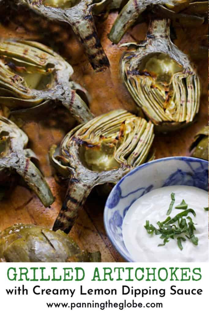 Pinterest Pin: 5 grilled artichoke halves and a bowl of lemon aioli with slivered basil in the middle