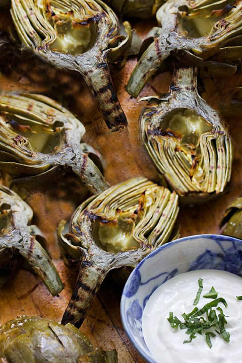 6 halved grilled artichokes on a wooden platter with a bowl of lemon aioli dipping sauce