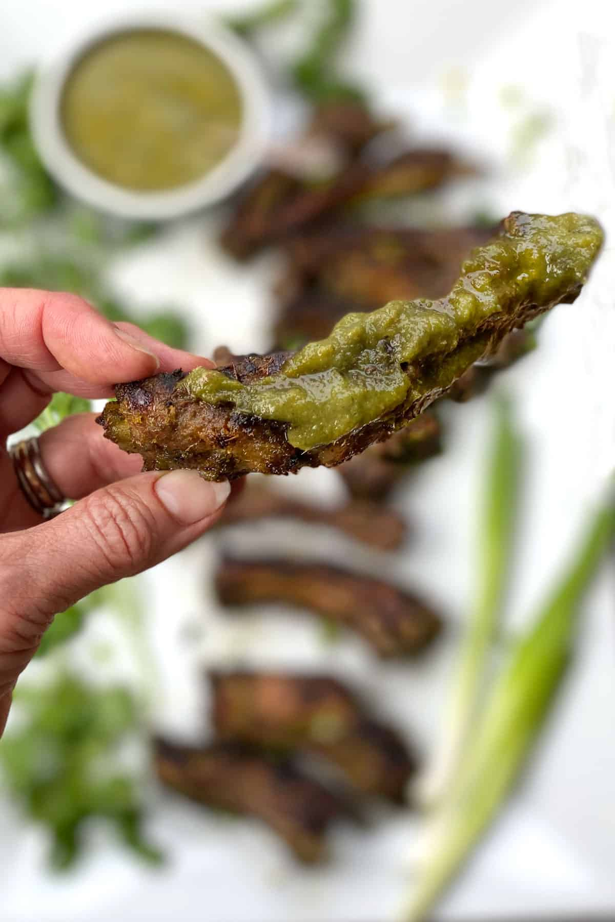 fingers holding one Thai BBQ rib coated with green bbq sauce, a platter of ribs in the background