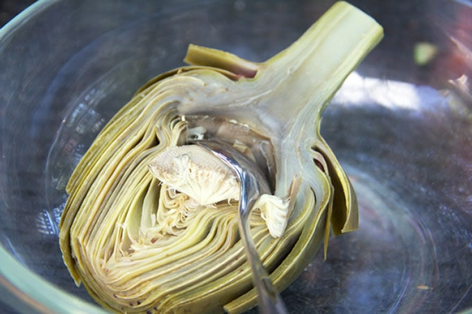 A halved artichoke that has been boiled and a spoon scooping out the choke, showing how easy it is to remove the choke after boiling or steaming.