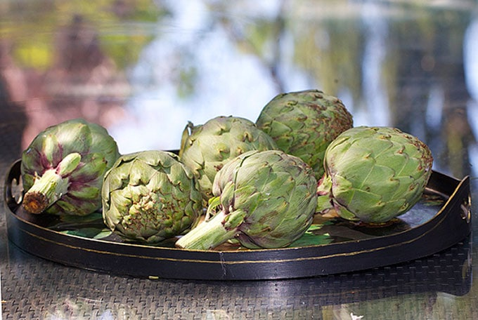 a platter of six raw artichokes