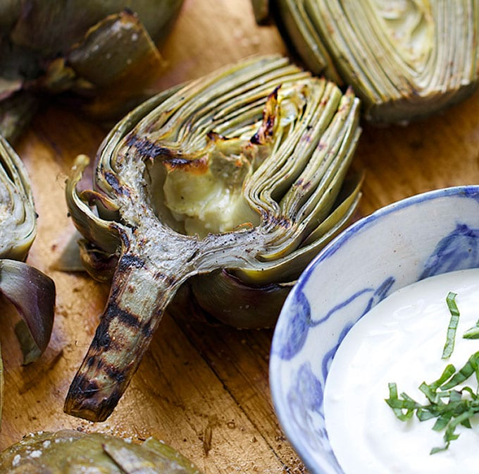 Grilled artichoke half next to a small bowl of lemon aioli.
