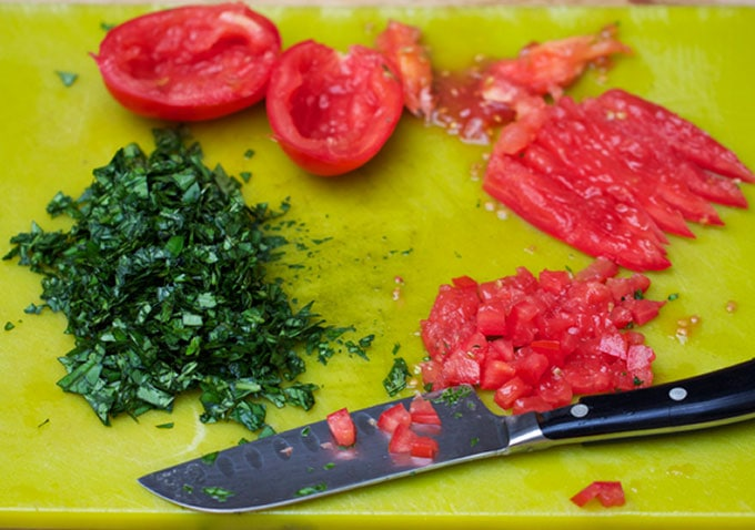 tomatoes and herbs on a chopping board to prep for three bean salad