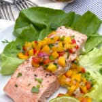 A piece of broiled salmon fillet on a bed of butter lettuce and topped with mango salsa