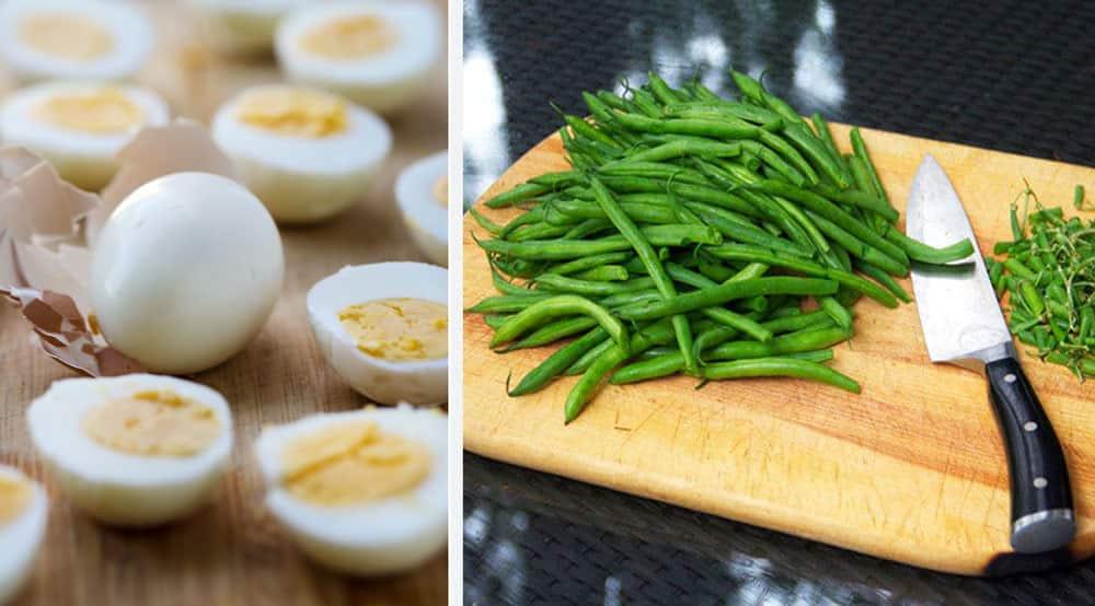 A bunch of hard boiled eggs on a counter, one peeled and whole, the others halved, and a cutting board with a pile of trimmed green beans on it